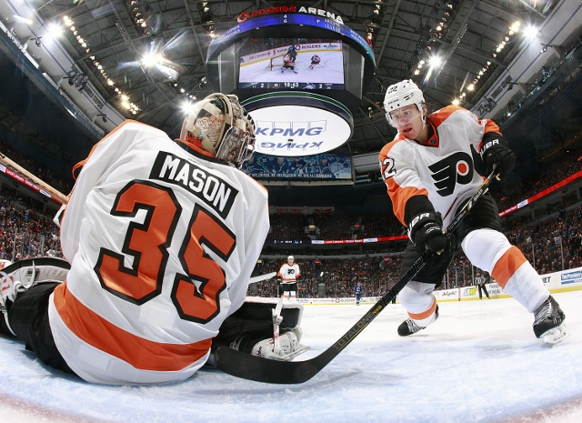 VANCOUVER, BC - DECEMBER 30:  Luke Schenn #22 keeps the puck from getting behind Steve Mason #35 of the Philadelphia Flyers as he makes a save during their NHL game against the Vancouver Canucks at Rogers Arena December 30, 2013 in Vancouver, British Colu