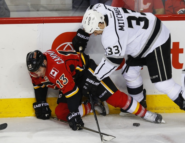 CALGARY, CANADA - FEBRUARY 27: Willie Mitchell #33 of the Los Angeles Kings knocks  Mike Cammalleri #13 if the Calgary Flames to the ice during the first period of their NHL hockey game at the Scotiabank Saddledome February 27, 2014 in Calgary, Alberta, C