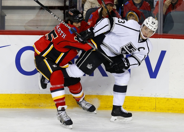 CALGARY, CANADA - FEBRUARY 27: Kevin Westgarth (L) of the Calgary Flames pushes Dustin Brown of the Los Angeles Kings away from the puck during the first period of their NHL hockey game at the Scotiabank Saddledome February 27, 2014 in Calgary, Alberta, C
