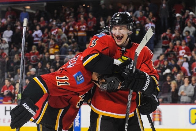 CALGARY, AB - FEBRUARY 1: Ladislav Smid #3 (L) congratulates Mikael Backlund #11 (R) of the Calgary Flames after Mikael Backlund scored the game-winning goal against the Minnesota Wild during an NHL game at Scotiabank Saddledome on February 1, 2014 in Cal