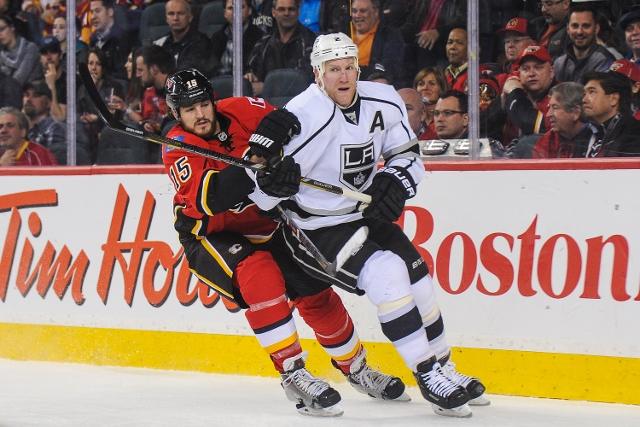 CALGARY, AB - APRIL 9: Kevin Westgarth #15 of the Calgary Flames chases the puck against Matt Greene #2 of the Los Angeles Kings during an NHL game at Scotiabank Saddledome on April 9, 2014 in Calgary, Alberta, Canada. (Photo by Derek Leung/Getty Images)