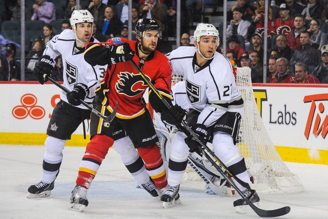 CALGARY, AB - APRIL 9: T.J. Galiardi #39 of the Calgary Flames looks for an opportunity in front of the net as Willie Mitchell #33 (L) and Alec Martinez #27 of the Los Angeles Kings defend during an NHL game at Scotiabank Saddledome on April 9, 2014 in Ca