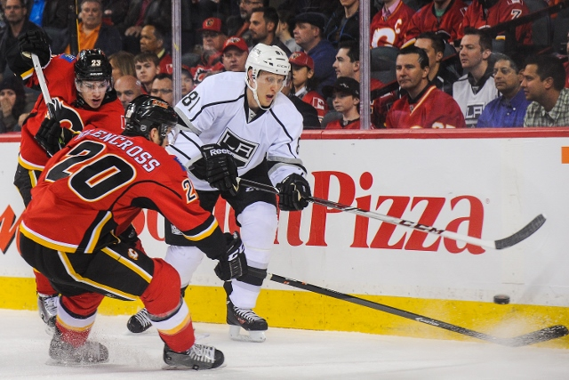 CALGARY, AB - APRIL 9: Curtis Glencross #20 of the Calgary Flames checks Andrew Campbell #81 of the Los Angeles Kings during an NHL game at Scotiabank Saddledome on April 9, 2014 in Calgary, Alberta, Canada. (Photo by Derek Leung/Getty Images)