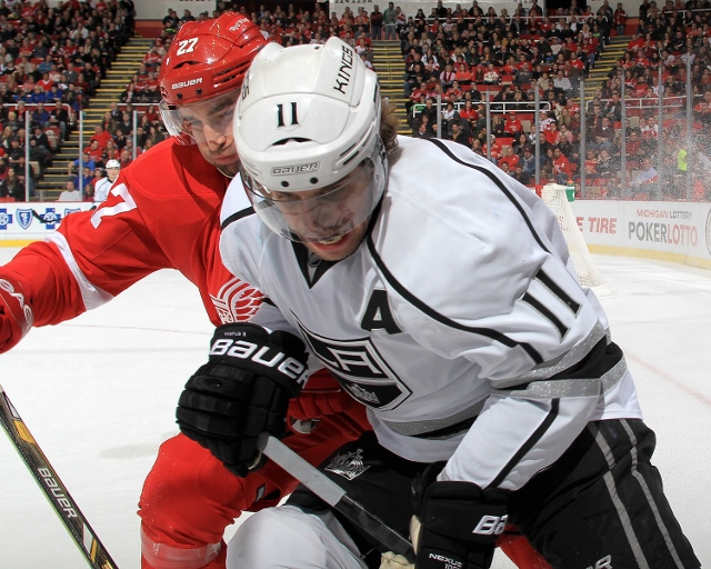 DETROIT, MI - JANUARY 18:  Kyle Quincey #27 of the Detroit Red Wings and Anze Kopitar #11 of the Los Angeles Kings battle in the corner for the puck during an NHL game on January 18, 2014 at Joe Louis Arena in Detroit, Michigan. (Photo by Dave Reginek/NHL