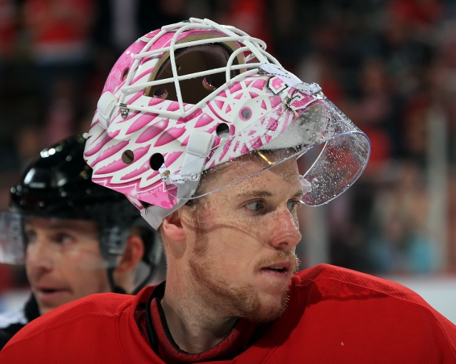 "DETROIT, MI - OCTOBER 23: Jimmy Howard #35 of the Detroit Red Wings looks down the ice with his custom painted mask for ""Hockey Fights Cancer"" night against the Pittsburgh Penguins during a NHL game on October 23, 2014 at Joe Louis Arena in Detroit, Michi"