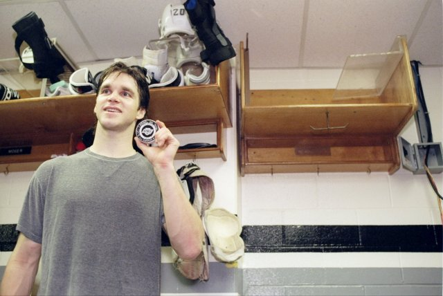 Luc Robitaille holds up the puck