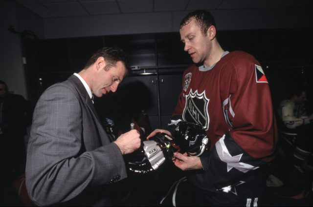 Dominik Hasek autographs a glove