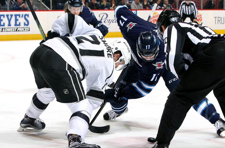 WINNIPEG, MB - MARCH 24: Nick Shore #21 of the Los Angeles Kings takes a second period face-off against Adam Lowry #17 of the Winnipeg Jets at the MTS Centre on March 24, 2016 in Winnipeg, Manitoba, Canada. (Photo by Jonathan Kozub/NHLI via Getty Images)