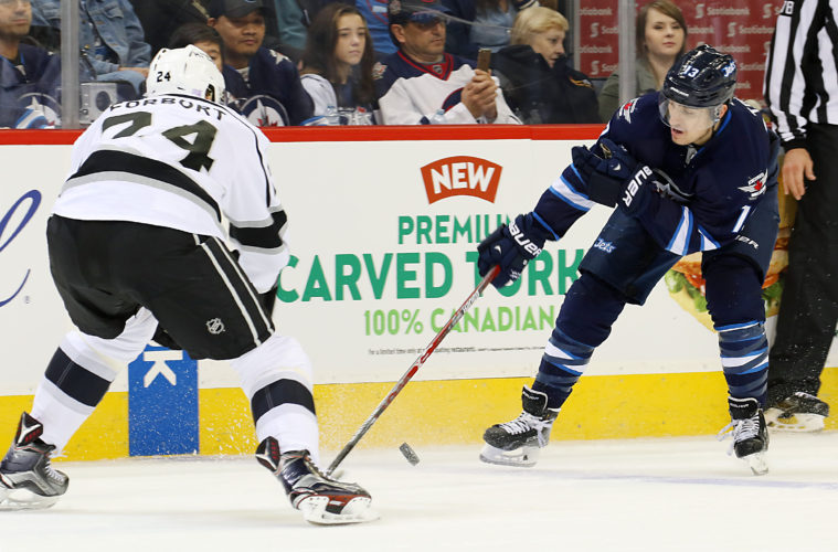 WINNIPEG, MB - NOVEMBER 13: Brandon Tanev #13 of the Winnipeg Jets plays the puck down the ice as Derek Forbort #24 of the Los Angeles Kings defends during second period action at the MTS Centre on November 13, 2016 in Winnipeg, Manitoba, Canada. (Photo by Jonathan Kozub/NHLI via Getty Images)